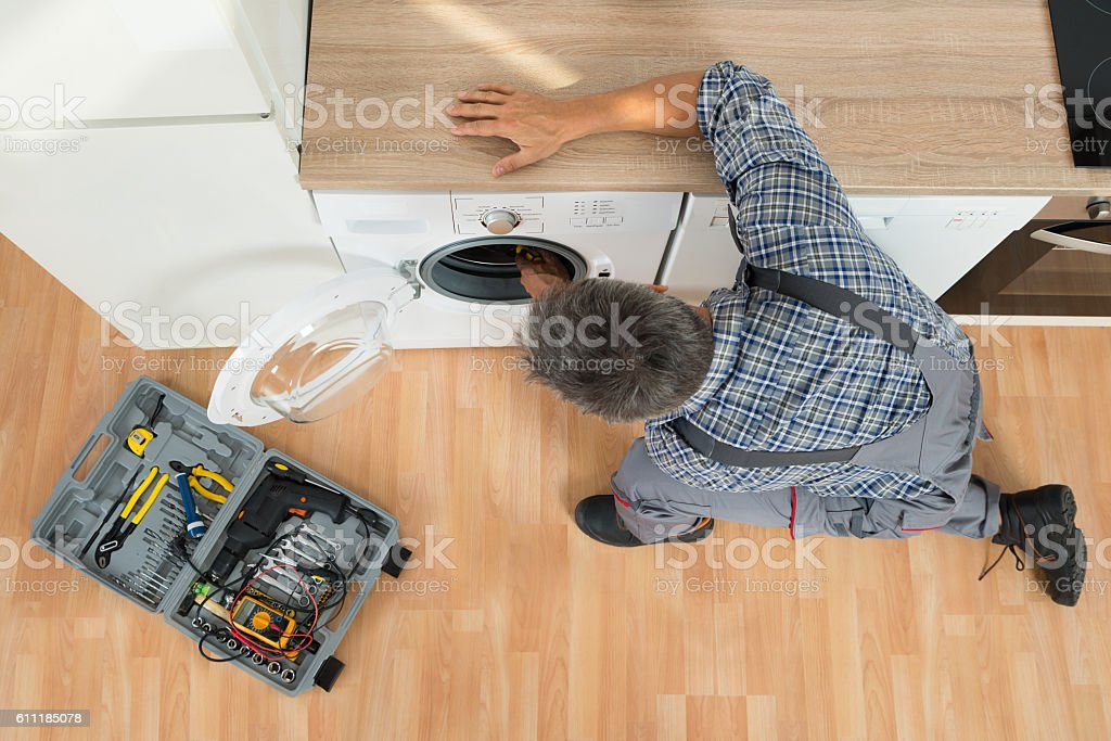 Handyman Checking Washing Machine At Home stock photo