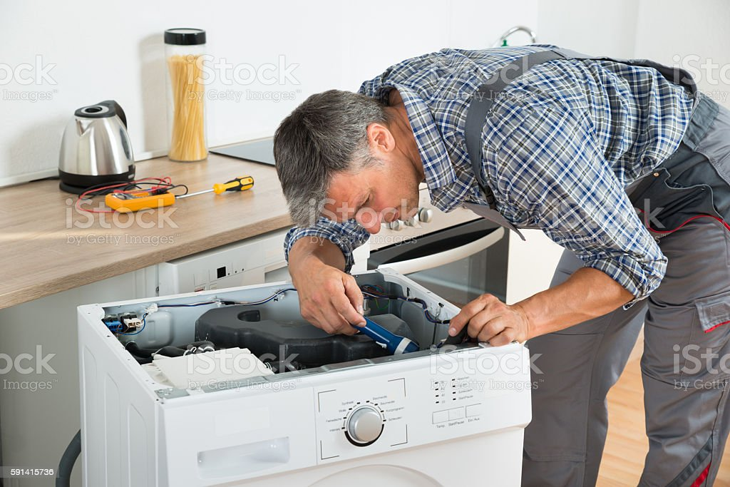 Handyman Checking Washing Machine With Flashlight stock photo