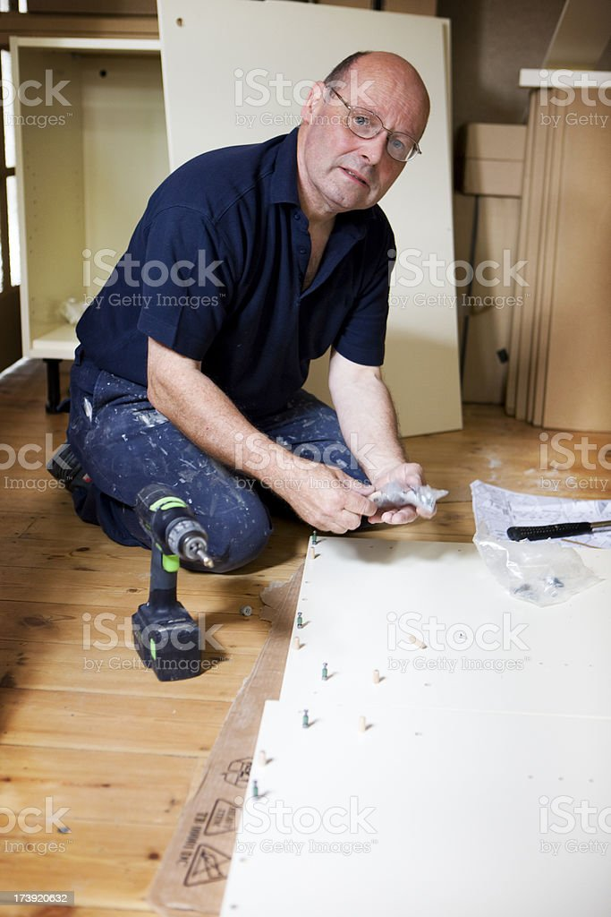 handyman constructing flat pack furniture royalty-free stock photo