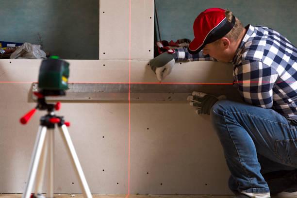 Bricoleur en traçant une ligne sur une cloison sèche avec l'aide de niveleur laser - Photo