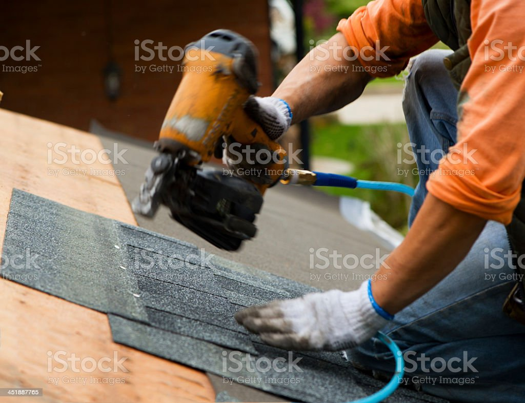 Handyman fitting tiles on the roof stock photo