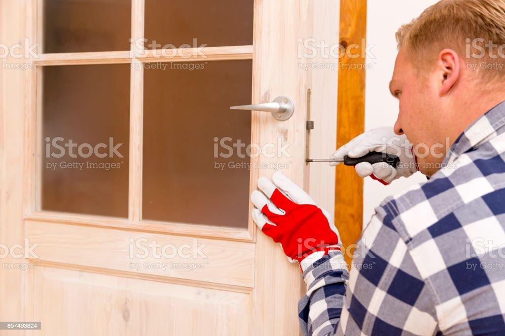 Handyman fixing the door with screwdriver stock photo