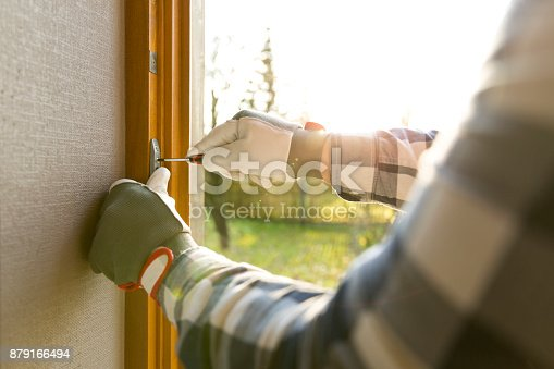 istock Handyman fixing the window with screwdriver 879166494