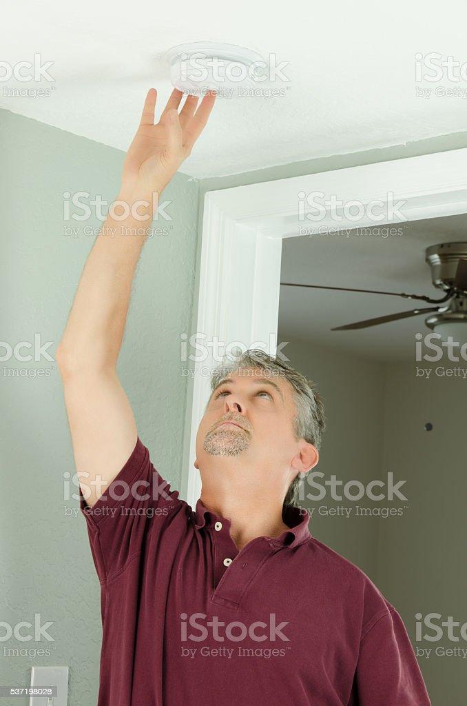 Handyman home owner checking smoke alarm testing bildbanksfoto