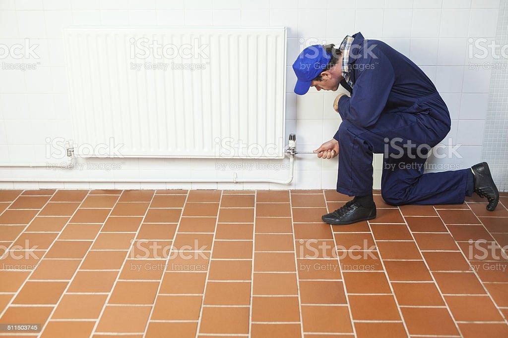 in blue boiler suit Mann für die Reparatur Heizkörper – Foto