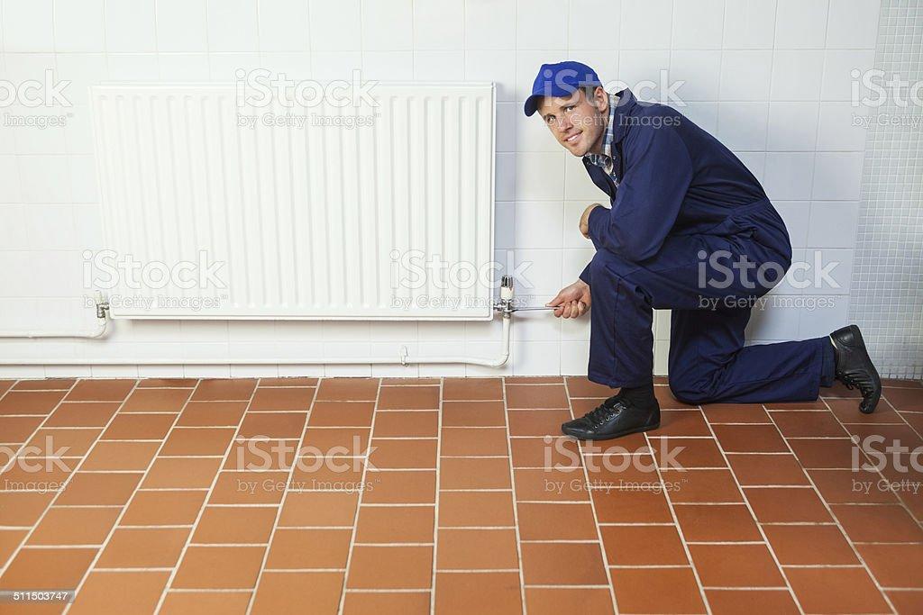 in blue boiler suit Mann für Reparatur Heizkörper – Foto