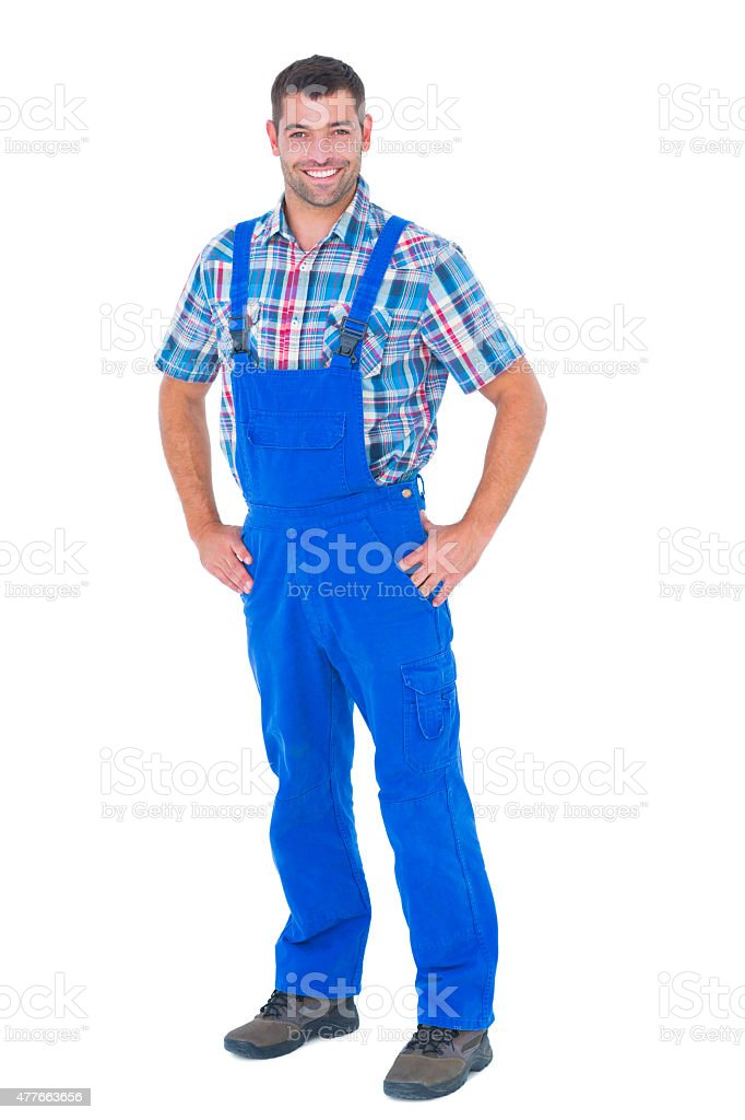 Handyman in coveralls standing hands on hip over white background stock photo