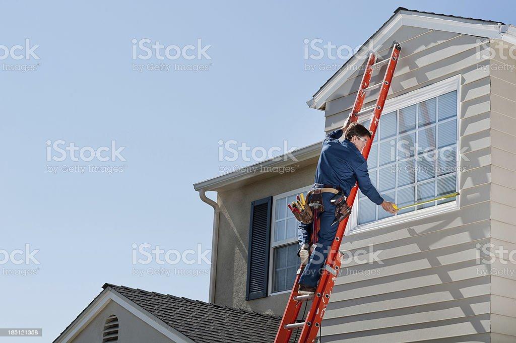 Handyman In Uniform Measuring Window stock photo