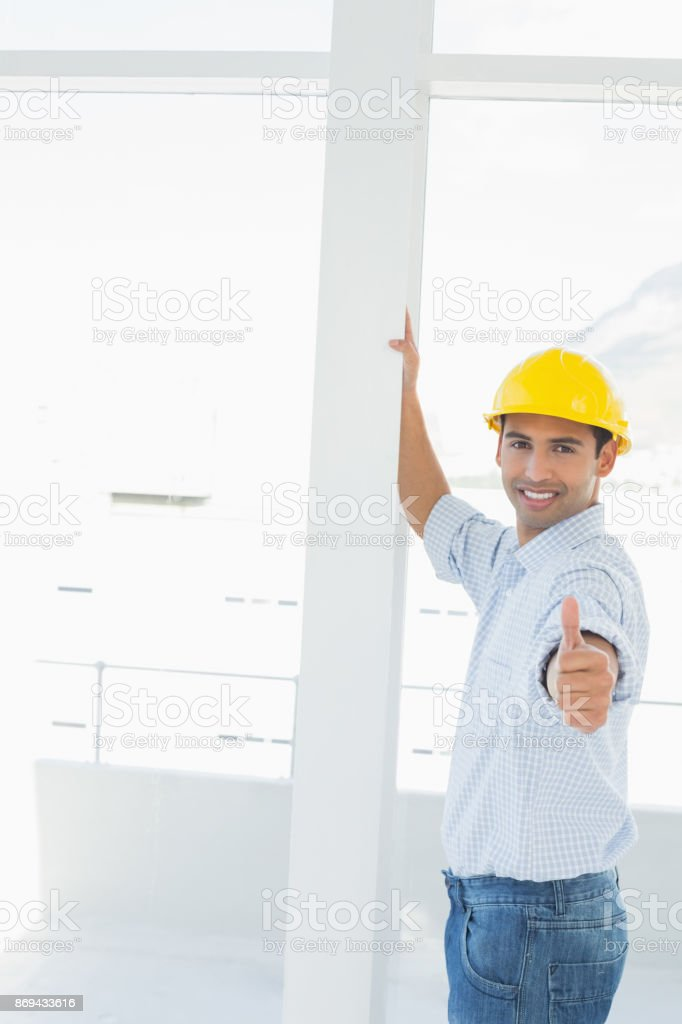 Handyman in yellow hard hat gesturing thumbs up in office stock photo