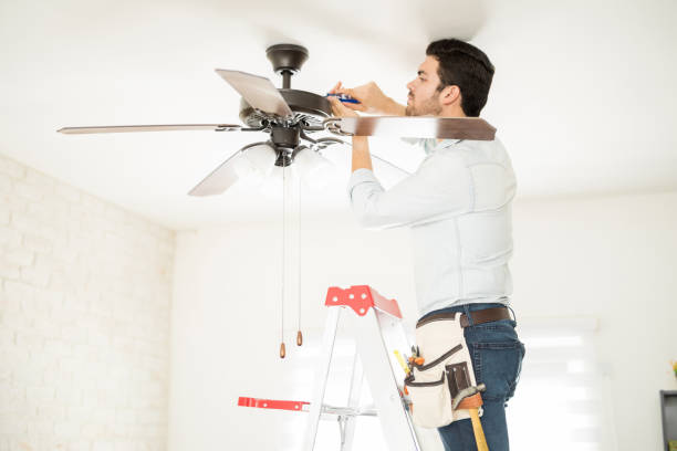 Handyman installing a ceiling fan Attractive young handyman stepping on a ladder and fixing a ceiling fan ceiling fan stock pictures, royalty-free photos & images