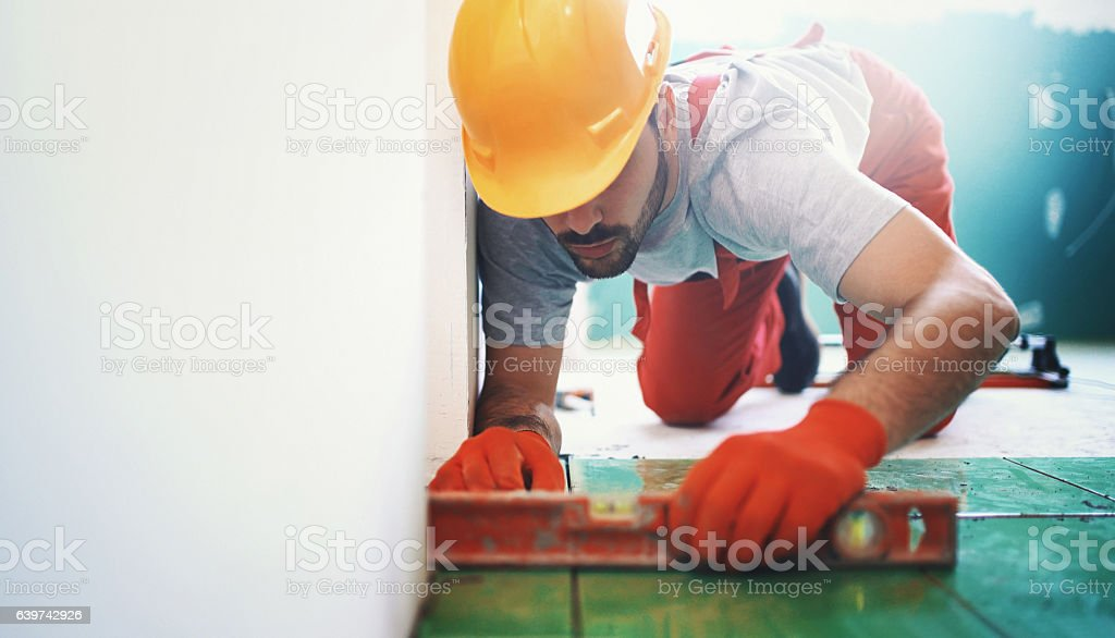 Handyman installing ceramic tiles. stock photo