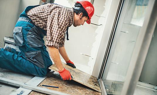 istock Handyman installing ceramic tiles. 681914034