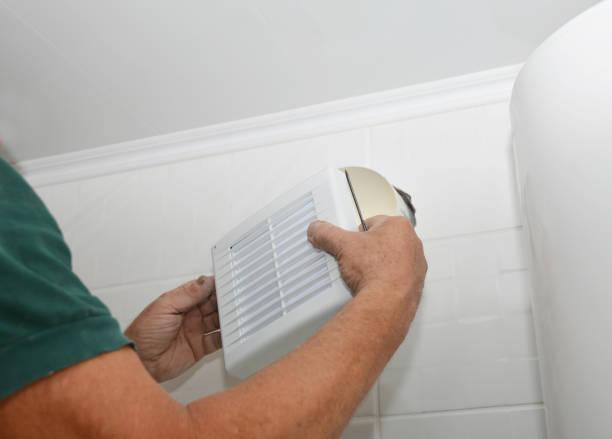 Klusjesman het installeren van nieuwe Bad vent ventilator, ventilatiesysteem in de badkamer van het huis. Bad fan reparatie, installatie. foto