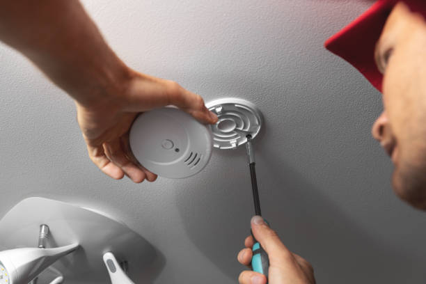 handyman installing smoke detector on ceiling at home stock photo