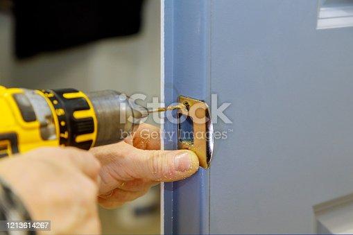 installing worker hands new door locker in the door lock