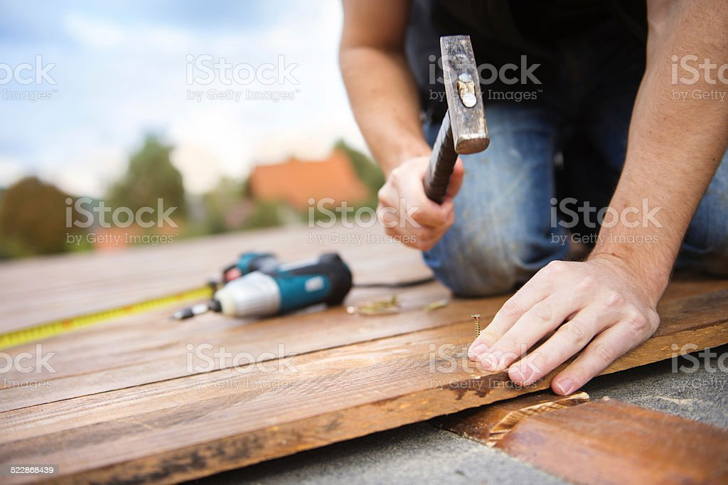 Handyman installing wooden flooring stock photo