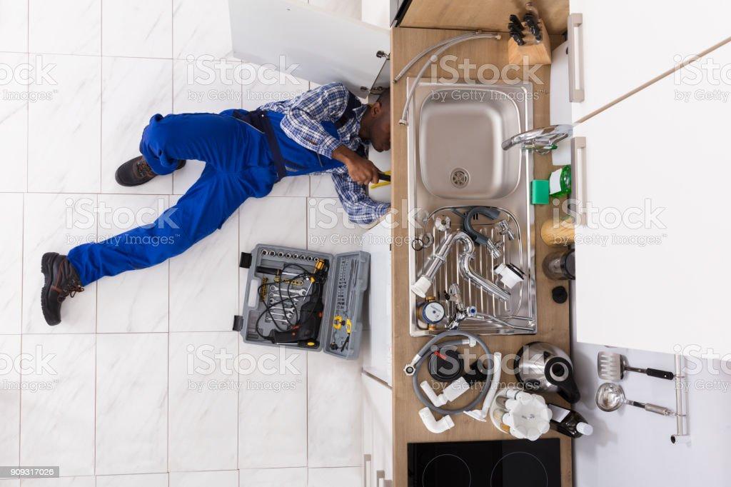Handyman Lying On Floor Repairing Sink stock photo