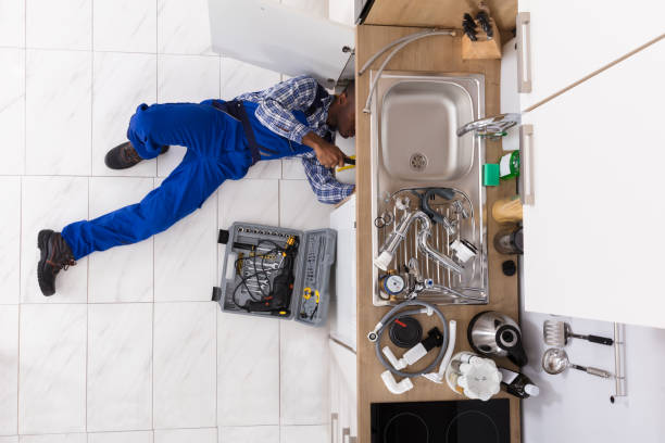 handyman lying on floor repairing sink - plumber stock photos and pictures