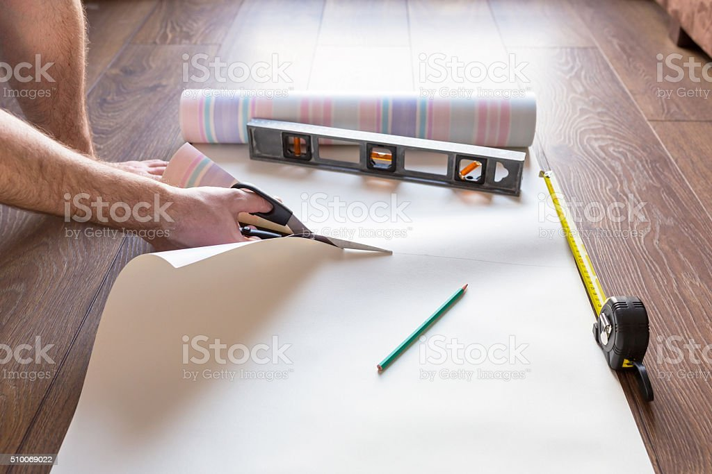 Handyman measuring wallpaper to cut stock photo
