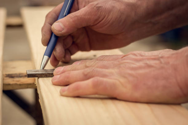 Handyman preparing wooden boards for cutting stock photo