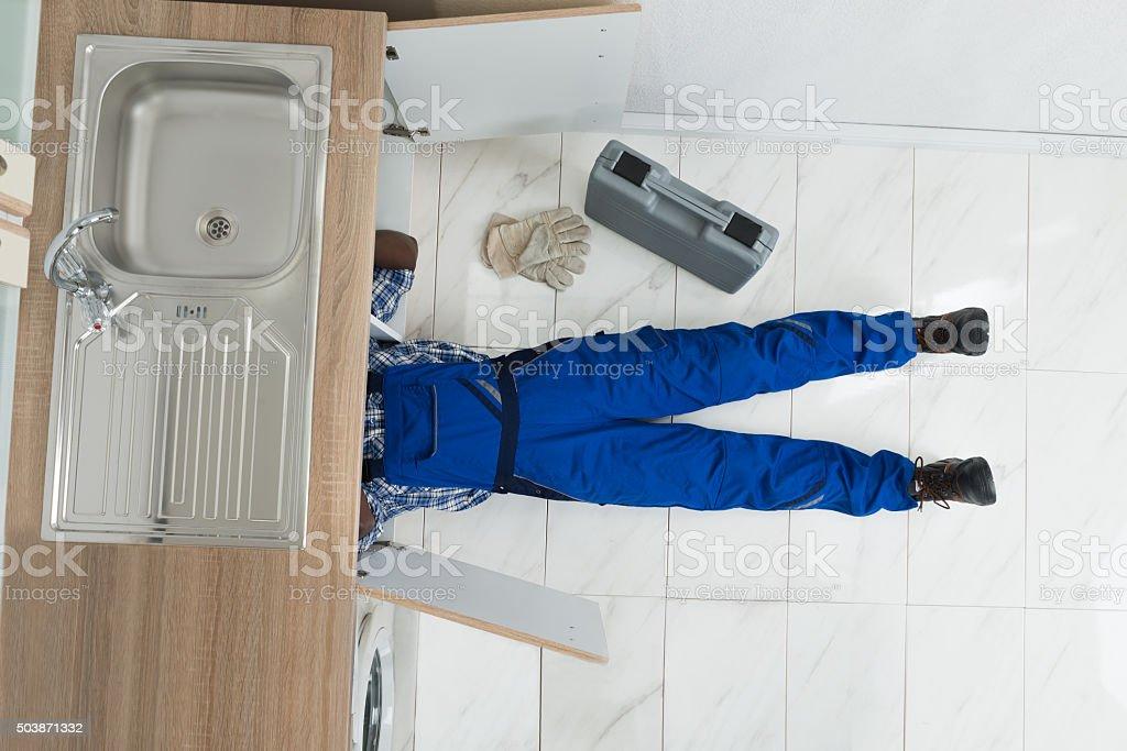 Handyman Repair Sink In Kitchen stock photo
