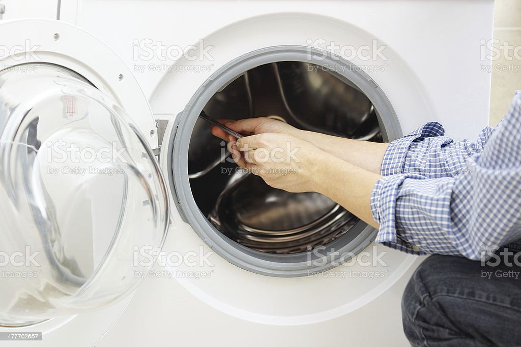 handyman repairing a washing machine stock photo