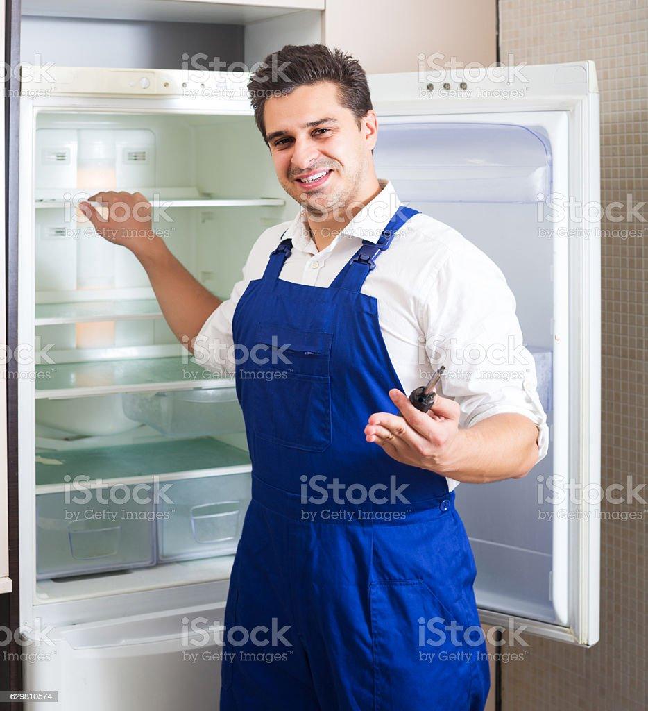 Handyman repairing refrigerator in kitchen stock photo
