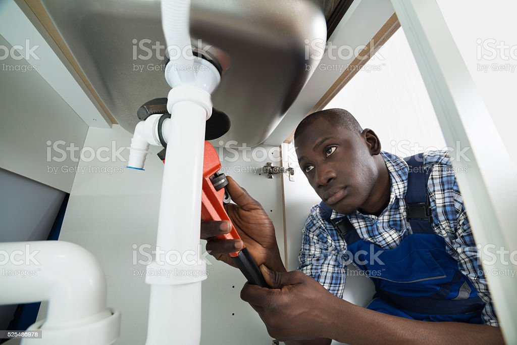 Handyman Repairing Sink Pipe stock photo