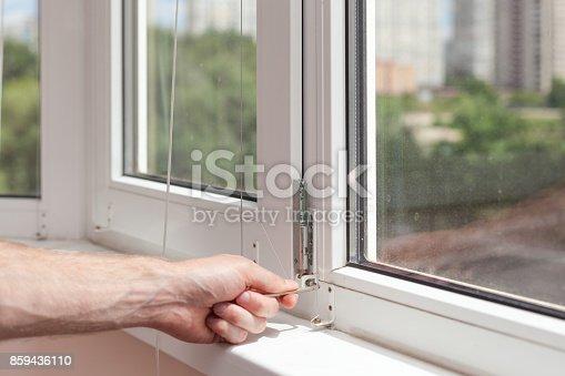 966792200 istock photo Handyman repairs plastic window with a hexagon. Workman adjusts the operation of the plastic window 859436110