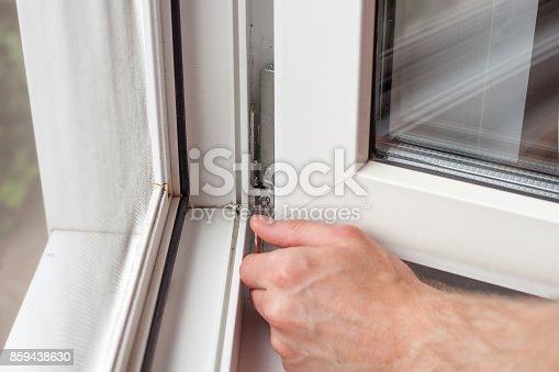 966792200 istock photo Handyman repairs plastic window with a hexagon. Workman adjusts the operation of the plastic window 859438630
