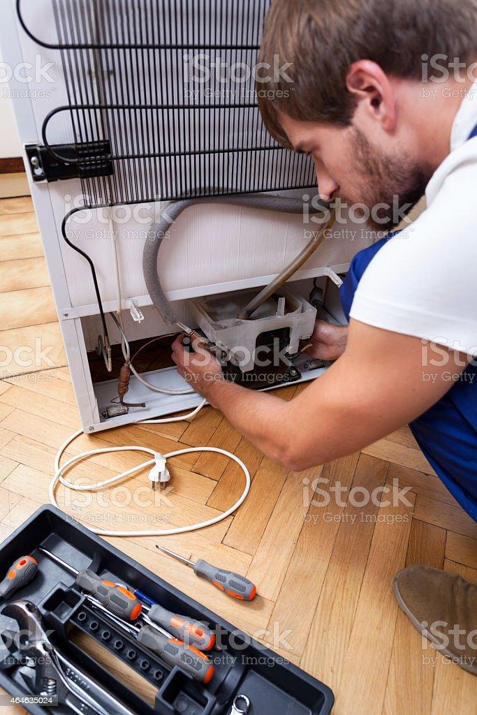 Handyman repairs the fridge stock photo