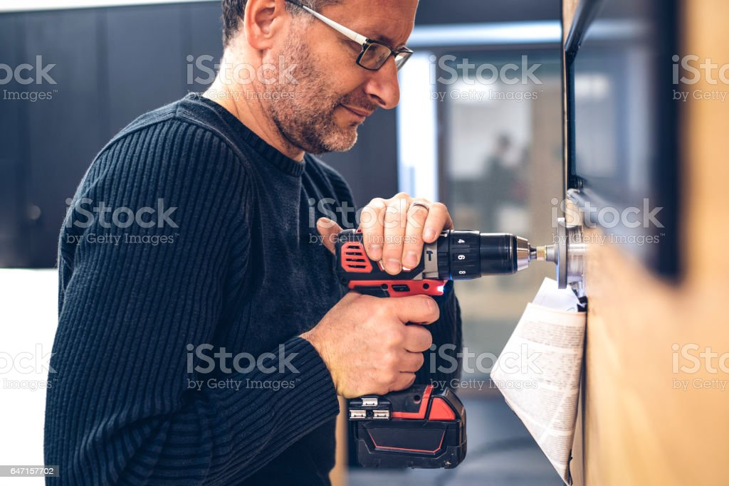 Handyman using a hole saw stock photo