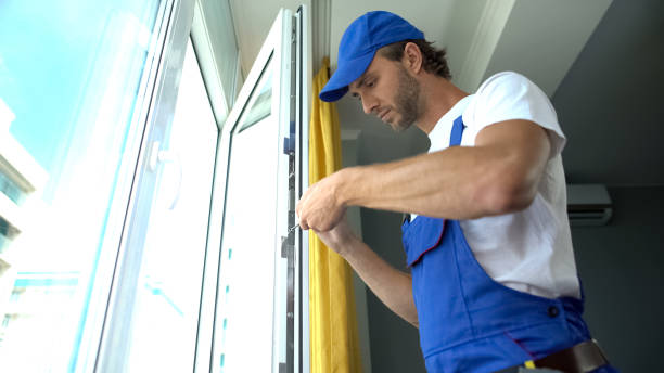 Handyman using screwdriver to fix window, repair and installation services stock photo
