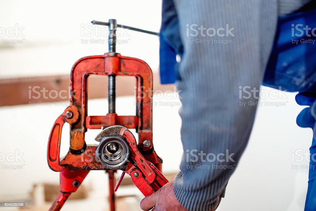 handyman using wrench at industrial plumbing stock photo