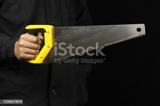 Handyman with hand saw in hand on black background