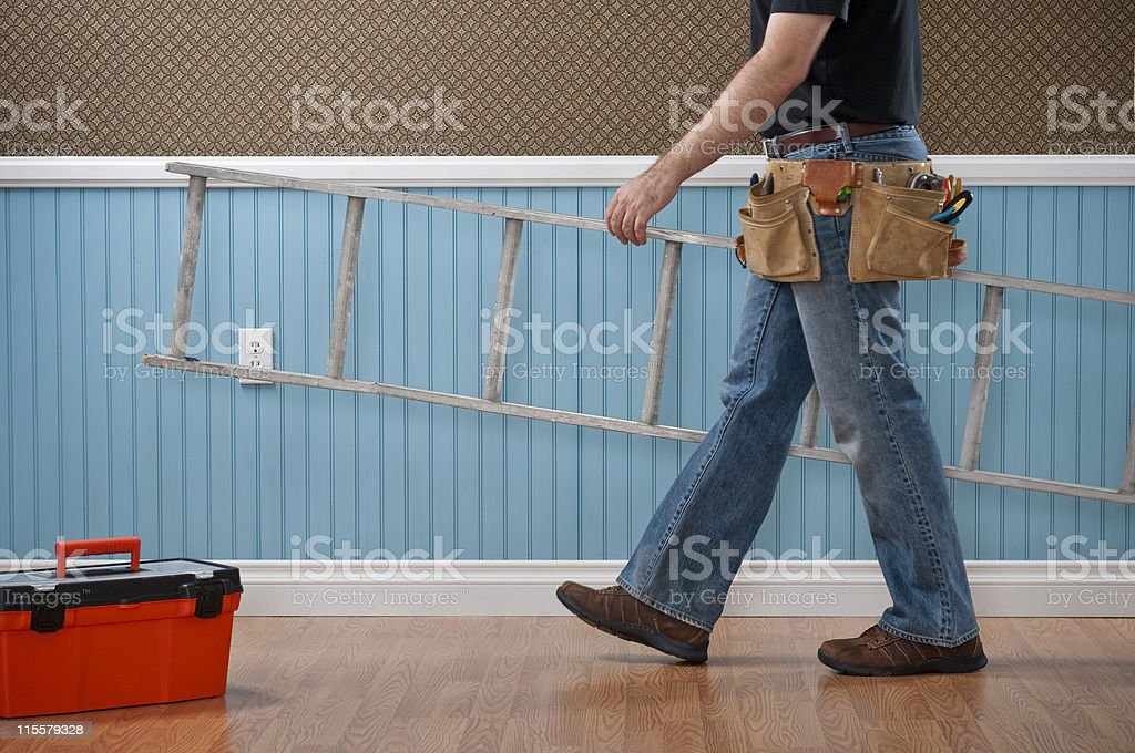 Handyman Working In Empty Room Male handyman with toolbox, tool belt and ladder  working in empty domestic room. The wall has a blue beadboard wainscoting and a patterned wallpaper. Adult Stock Photo
