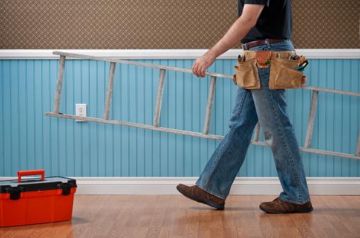 Handyman Working In Empty Room Stock Photo - Download Image Now