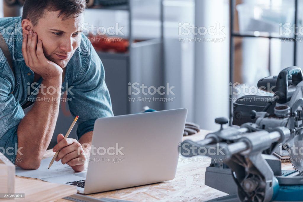 Handyman working using laptop stock photo