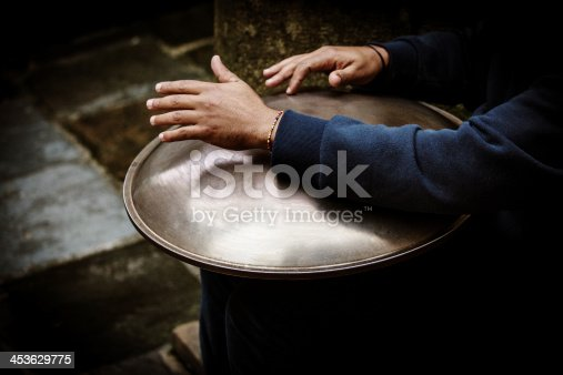 Street performer playing a traditional Hang drum, the Hang is a percussion instrument that is inspired by mixing the Gong, Gamelan, Steel Pan and the Ghatam other traditional instruments.