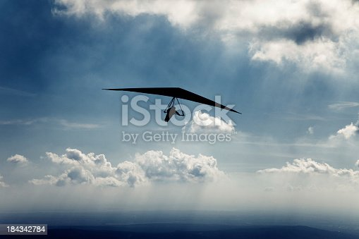 Hang glider against dramatic sky. Sun-rays coming out from the clouds.