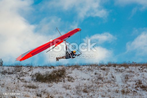 istock Hang glider pilot flies low above training slope. Learning to fly 1301139166