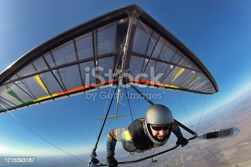 Hang glider pilot with his colorful wing flies high far away from other people. Concept of unning from crowd,self isolation and social distancing