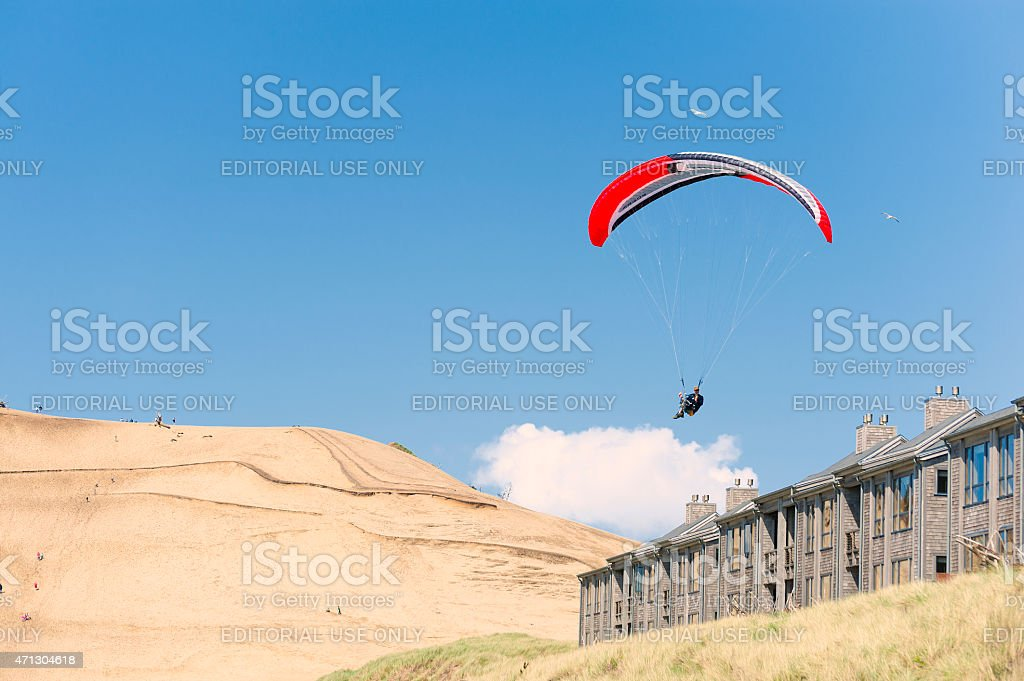 Hang glider soars over beach lodging at Pacific City stock photo