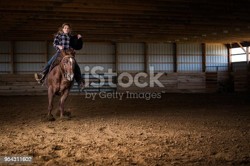 Pretty blond Caucasian female in her 20's wearing denim jeans and a plaid shirt rides her Dun colored quarter horse who practices reining into an abrupt sliding stop in a training barn on a cattle ranch, Indiana, USA