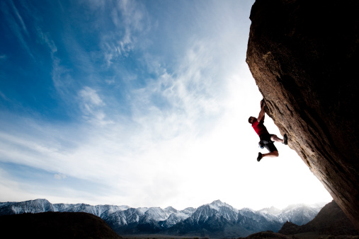 A climber hanging on to a steep cliff.