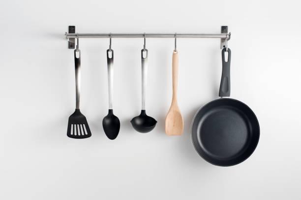 hanged kitchen utensils pans and utensils hanging on kitchen wall - przybór kuchenny zdjęcia i obrazy z banku zdjęć