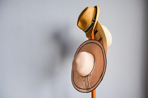 Hanger rack with summer wicker brimmed hats