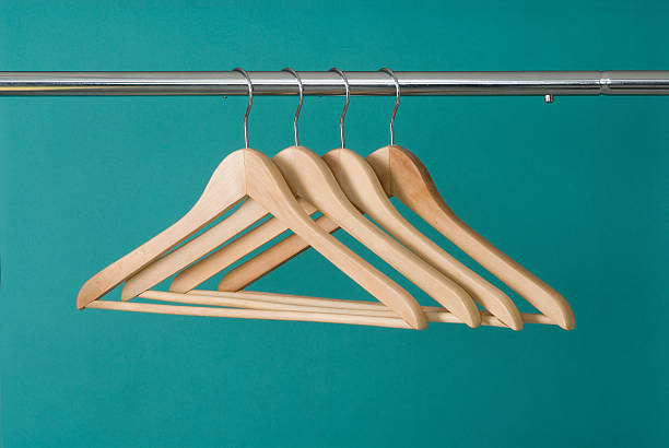 Hangers On Pole Four wooden hangers on chrome pole with a green background. coathanger stock pictures, royalty-free photos & images