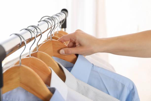 kleiderbügel mit hemden und weiblicher hand vor hellem hintergrund, platz für text - geschäftskleidung stock-fotos und bilder