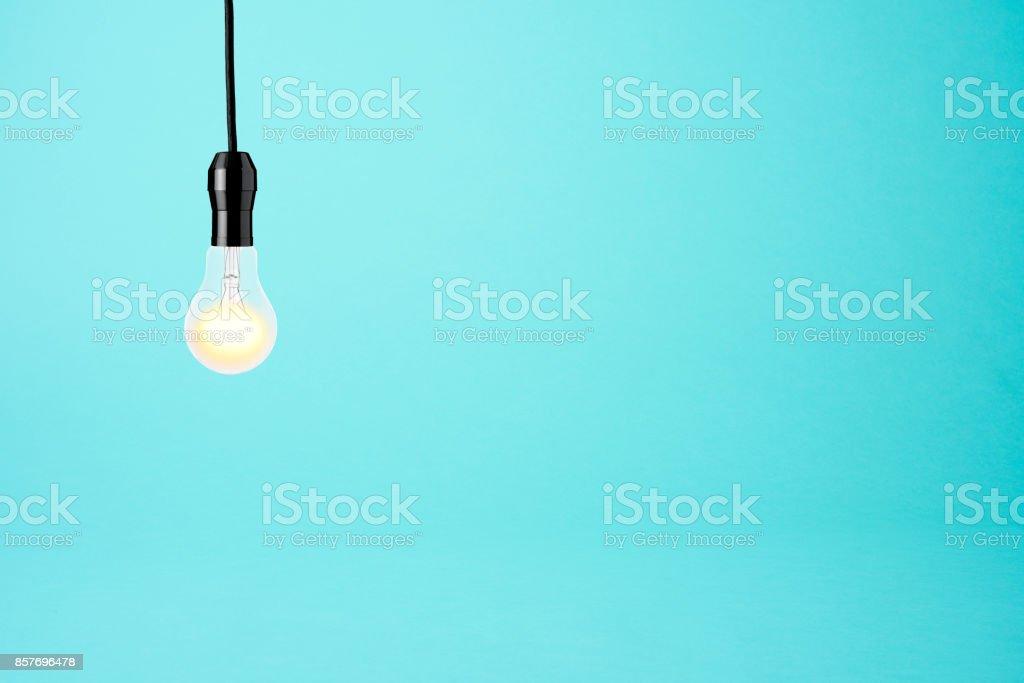 Hanging a illuminated light bulb on blue background stock photo